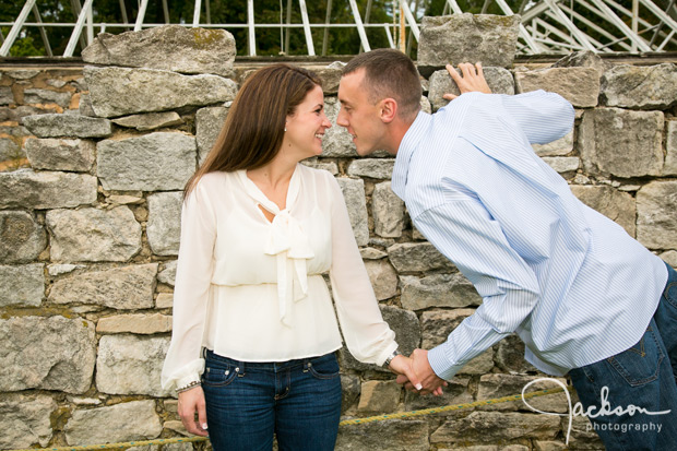couple playfully posing in front of stone wall