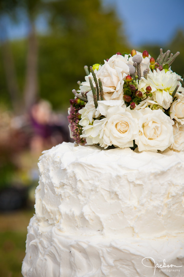 detail of white stucco cake and green brown flowers