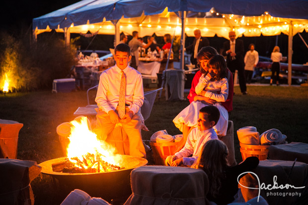 people sitting at campfire at wedding reception