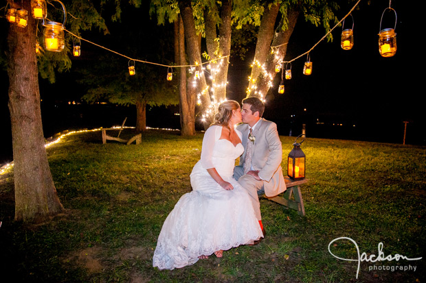 bride and groom kissing under candles hanging from trees
