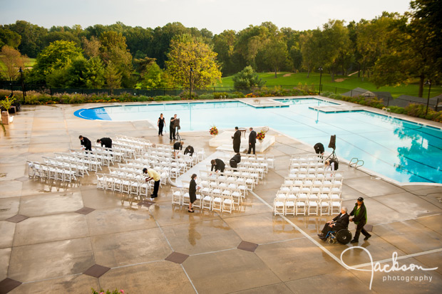 staff wiping down wet wedding ceremony chairs