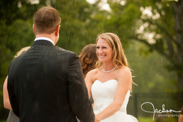 bride smiling during ceremony in the rain