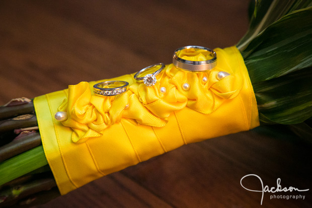 bride and groom rings on yellow bouquet wrappings