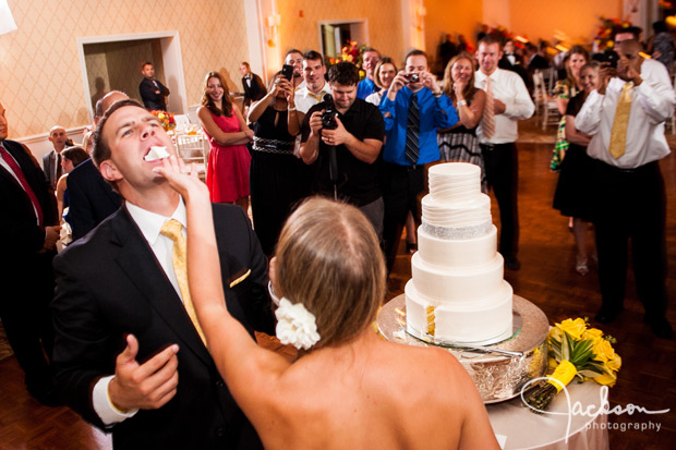 bride shoving cake in the face of the groom