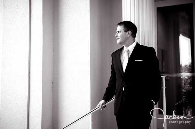 groom leaning on railing
