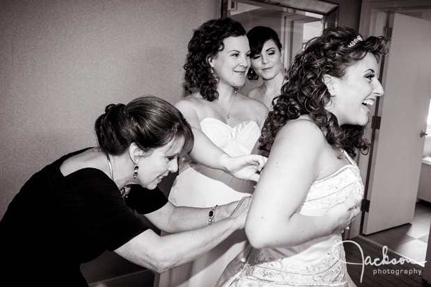 family tying bride's dress