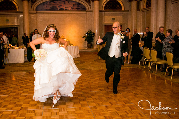 bride and groom entering reception with gold chain and glasses