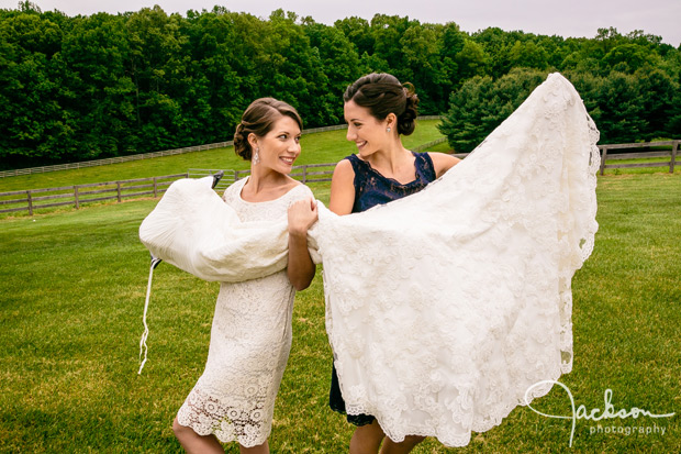 bride and sister holding dress