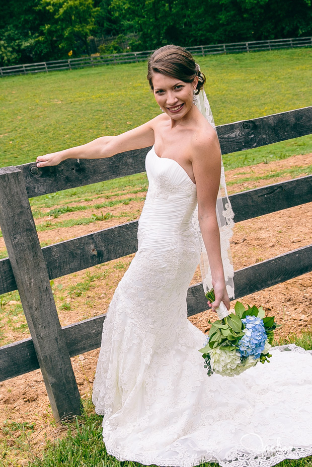 bride along wooden fence with blue green flowers